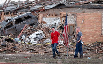 Two men stand in front of Plaza Towers Elementary after a tornado destroyed the school on Monday.