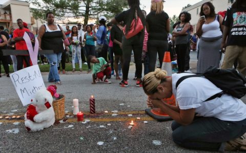 Meghan O'Donnell, 29, from St. Louis, prays at the spot where Michael Brown was killed Sunday evening