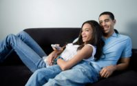 african american couple on couch watching tv