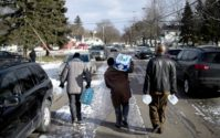 Flint residents Marcus Shelton, from left, Roland Young, and Darius Martin walk on an ice-covered street as they retrieve free water. AP