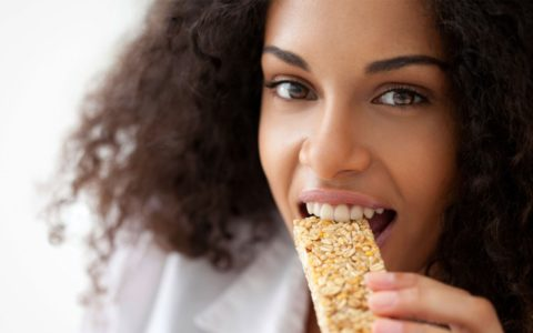 african american woman eating a healthy granola bar