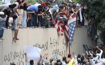 Protesters destroy an American flag