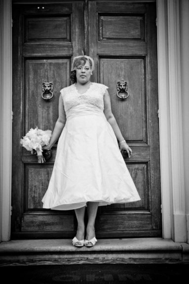 An a-line dress made for a goddess! The bride <em>Ivori Lipscomb-Warren</em> poses against these astounding ancient double-doors