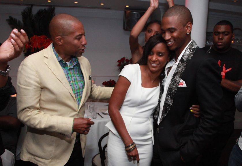 Trey Songz hugs his mother as manager Kevin Liles looks on