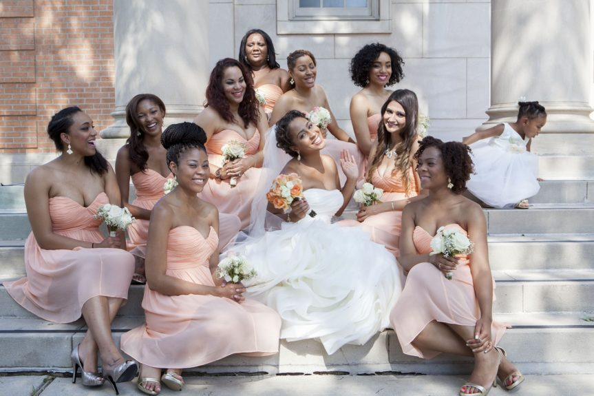 The bride laughing with her beautiful bridesmaids, who are wearing peach Donna Morgan dresses