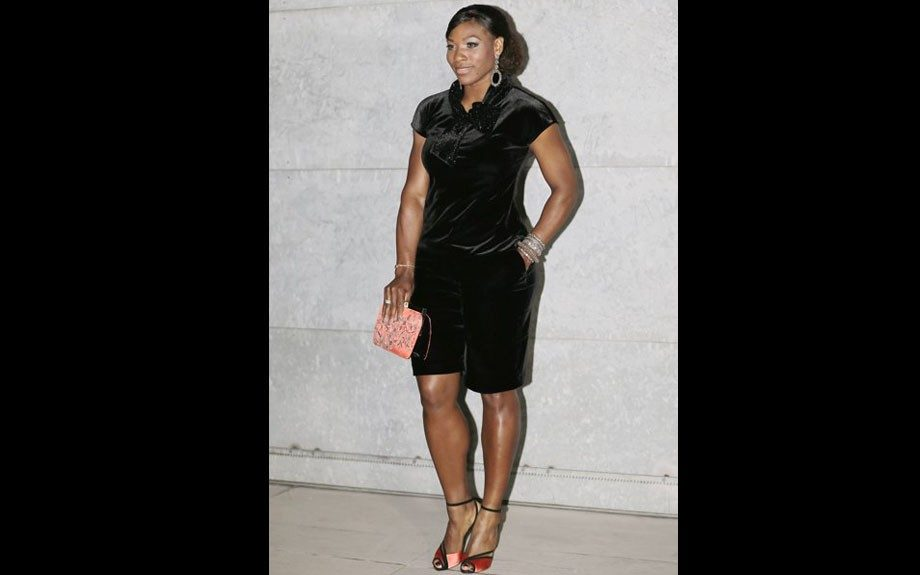 Serena Williams wore a black velvet playsuit, a red satin floral clutch, and red satin ankle-strap sandals.