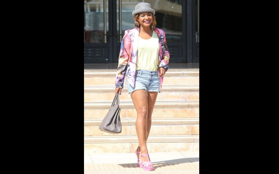 Christina Milian wears a Nicola Finetti cropped jacket, gray hat, t-shirt, denim cut offs, pink Yves Saint Laurent Tribute sandals and a grey Birkin bag.
