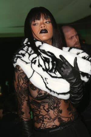 Rihanna bares a bit of skin in a lace top at the Gaultier show.