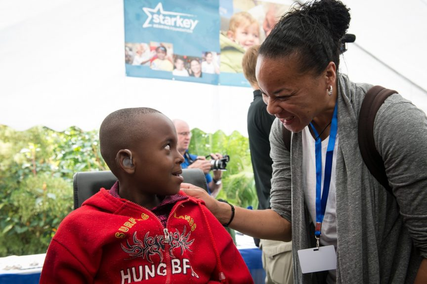 Dawn Staley, head coach of the South Carolina Gamecocks, provides hearing aids to a young boy in Rwanda.