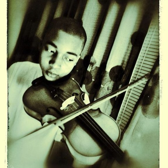 """Che and his violin. """"Che is hardworking. He is unique. I admire his practice on the violin,"""" Amal says."""