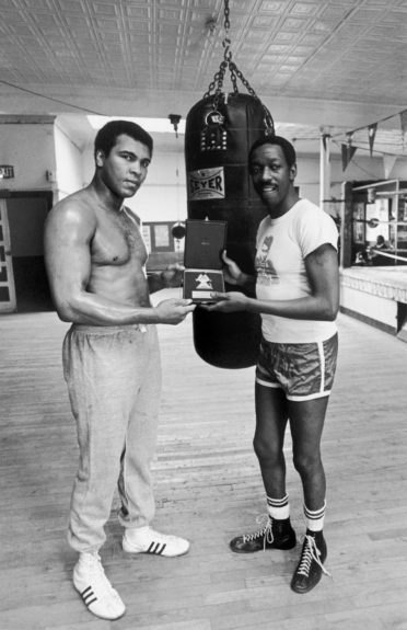 <p> Heavyweight boxing champion Muhammad Ali receives a plaque from Italy's T.V. Magazine via singer Alvin Cash in 1977 (Ozier Muhammad/Ebony Collection)</p>