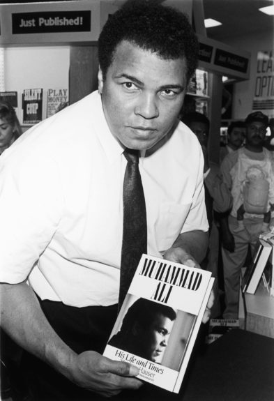 <p> Muhammad Ali holding up a copy of his book 'Muhammad Ali: His Life and Times' written by Thomas Hauser, in 1991 (Frederick Watkins,Jr./Ebony Collection)</p>