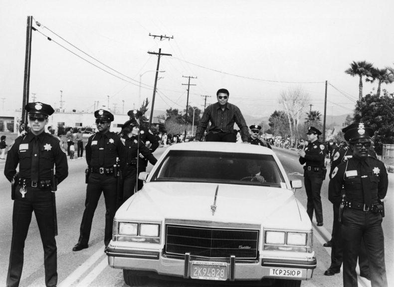 <p> Muhammad Ali appears atop a Cadillac flanked by police officers during the Black History Parade in Santa Ana, CA in 1985 (Isaac Sutton/Ebony Collection)</p>