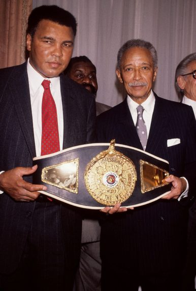 <p> Three time heavyweight boxing champion Muhammad Ali is given the first ever Victor Potamkin award belt by Mayor David Dinkinsin 1992 in New York(Frederick Watkins, Jr./Ebony Collection)</p>