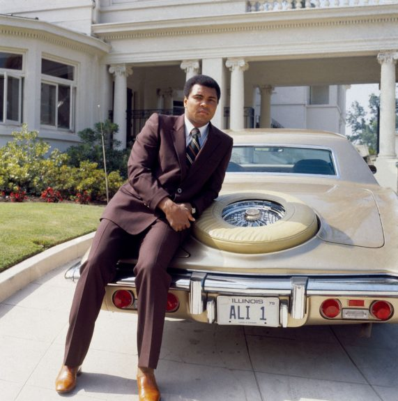 <p> Muhammad Ali stands in front of his Chicago estate, leaning against his Lincoln with personalized plates in 1979 (Isaac Sutton/Ebony Collection)</p>