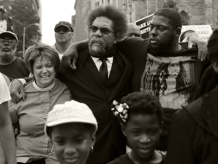 <p> 	FERGUSON: Cornel West, center, flanked by activists Tory Wilson, right, and the Rev. Renita Lamkin, left, march to the Thomas F. Eagleton Federal Courthouse, Monday, Aug. 10, 2015, in St. Louis. Several protesters were arrested at the courthouse. (AP Photo/Jeff Roberson)</p>