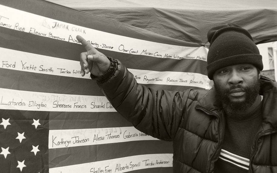 <p> 	MINNEAPOLIS: Jamine Robinson points to the name of his brother, Jamar Clark, on an upside-down flag bearing names of people killed at the hands of police outside the Minneapolis Police Department's Fourth Precinct, Tuesday, Nov. 17, 2015, in Minneapolis... (AP Photo/Jim Mone)</p>