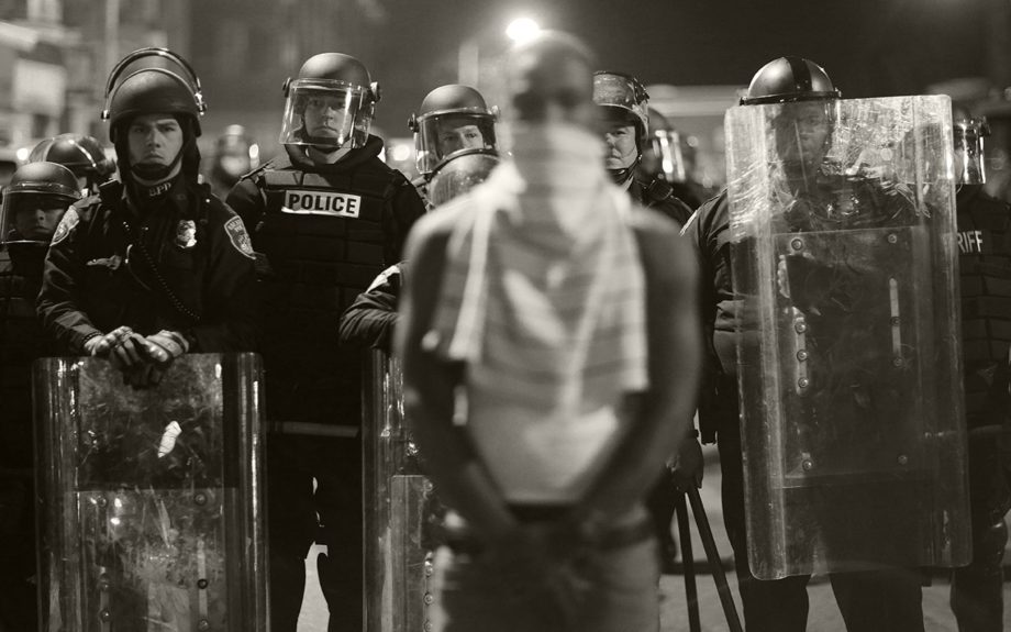 <p> 	BALTIMORE: A man stands in front of a line of police officers in riot gear as part of a community effort to disperse the crowd ahead of a 10 p.m. curfew in the wake of Monday's riots following the funeral for Freddie Gray, Tuesday, April 28, 2015, in Baltimore. (AP Photo/David Goldman)</p>
