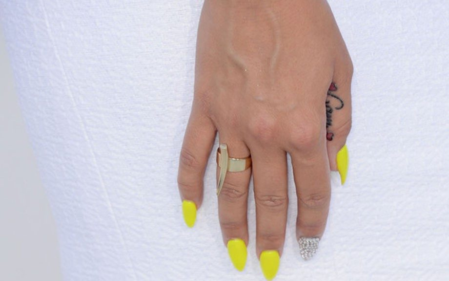 She paired her hoop earrings with a gold bar ring and electric yellow and bling manicure