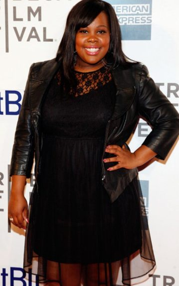 Amber Riley poses in a biker-chic ensemble pairing a black dress with a lace overlay with a black leather jacket.