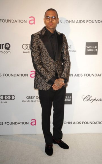 Chris Brown jetted back from Hawaii but he clearly changed out of his plane clothes, dressed in an Angelo Galasso suit, Alberta Ferretti loafers and Thom Browne glasses. Photo Credit: Getty