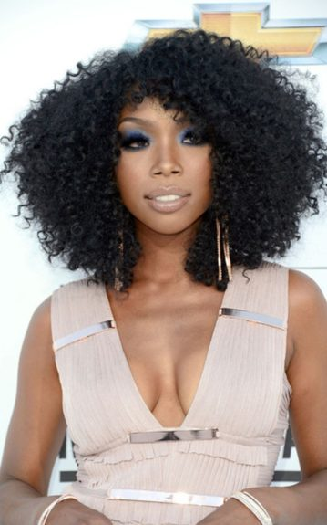 Brandy rocked a curly blowout with rose gold drop earrings and a blue shimmery eye shadow