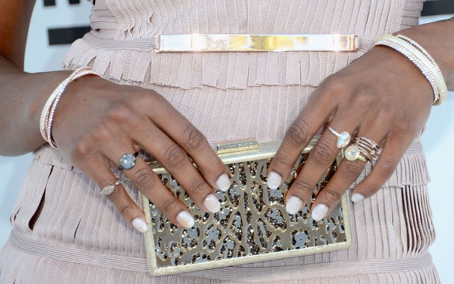 Her rose gold rings and bracelets complimented her simple pearl-like manicure and gold clutch