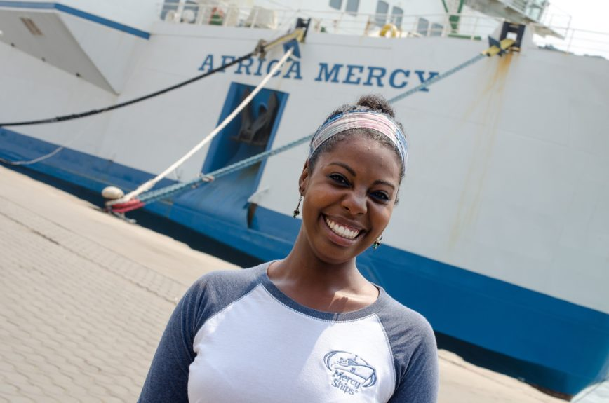 Tori Hobson stands in front of a docked Mercy Ship