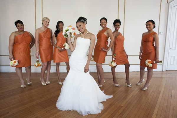 The bridal party has their girl's back, looking stunning in burnt orange dresses.