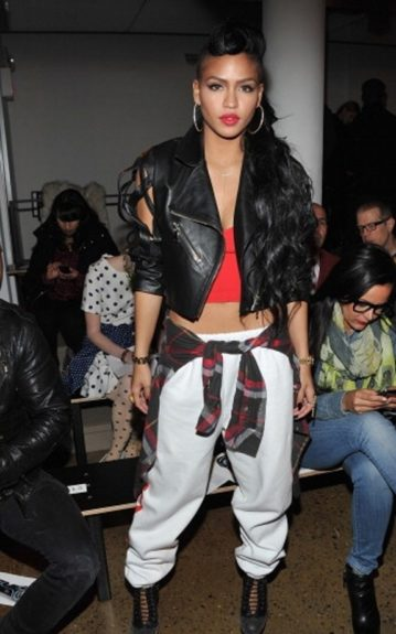 Cassie pulls all of the colors from her outfit together by pairing the red black and white tied shirt with a red top and lipstick, a black biker jacket and a pair of white sweats