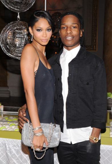 Hanging with her beau A$AP Rocky, she's striking in this black jumpsuit with cutouts and silver jeweled bag, while he matches her blackout, pairing it with a white button down.