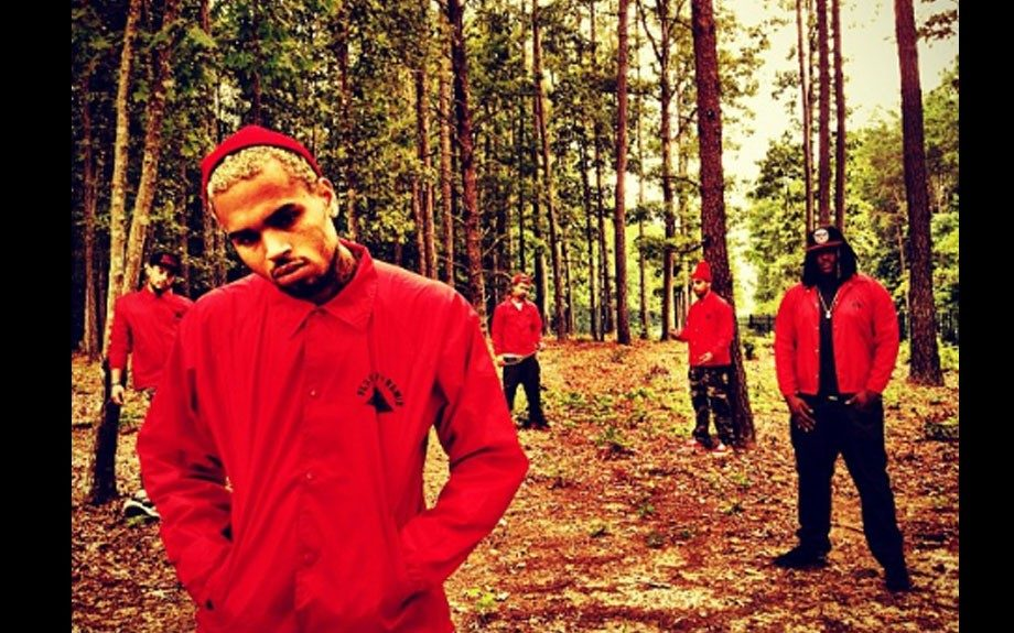 Chris models his own clothing line, wearing a red Mechanical Dummy track jacket
