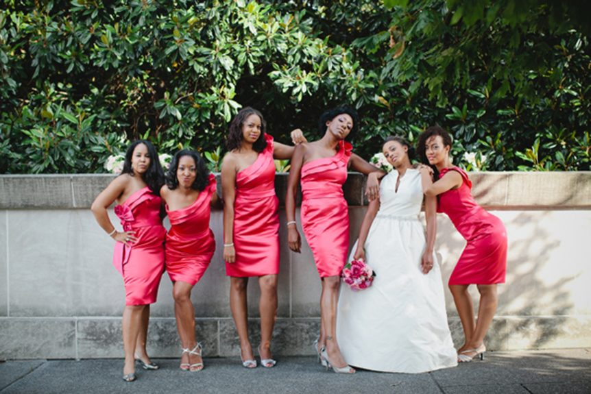 The bride D'Ann Redd joins her bridal party for a silly pose. The ladies wore satin fuchsia one-shouldered sheath dresses