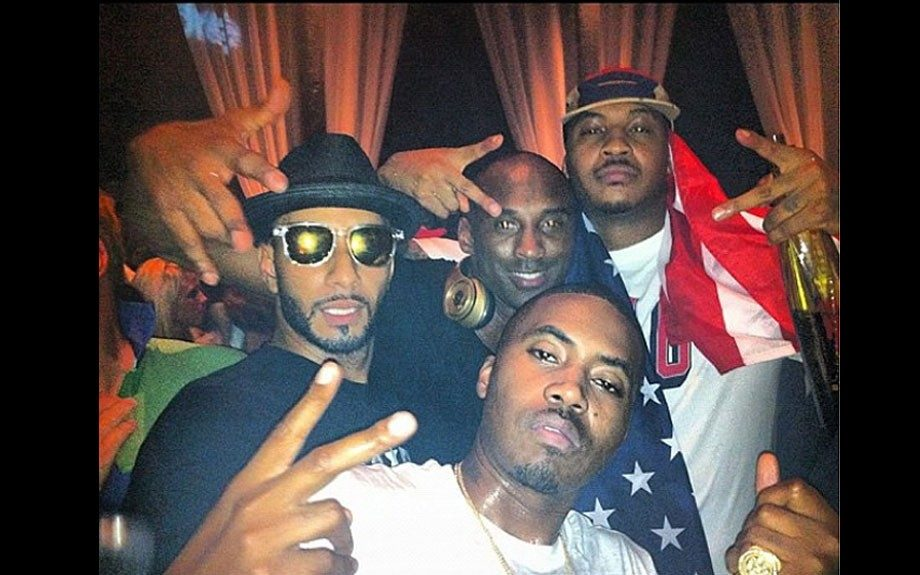 Carmelo wears a white t-shirt with red and blue print, a fitted cap, and a flag. Swizz Beats wears a black hat, sunglasses, and a black t-shirt; Kobe wears a black t-shirt as well, while Nas wears a white t-shirt with blue print. Photo Credit: Carmelo Anthony's Instagram