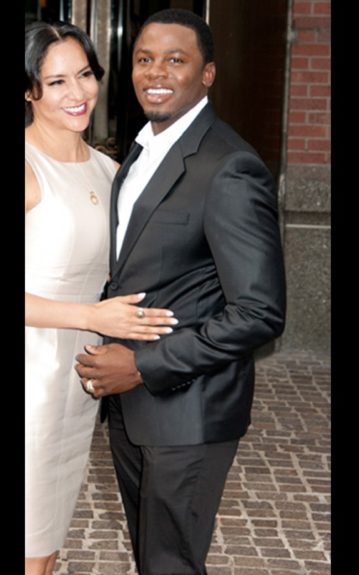 Derek Luke wears a black tuxedo with a hint of shine, a white button down, and his wife wears a cream knee-length dress. Photo Credit: Getty
