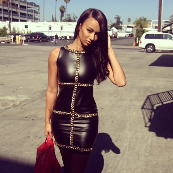 Draya gave us some bad girl edginess that we're digging in a black leather Queen Russia dress with gold chain detail, and red tote. <em>Photo</em>: Draya's Instagram