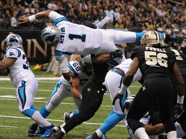 <p> 	Carolina Panthers quarterback Cam Newton (1) dives over the New Orleans Saints defensive line for a touchdown. Jeff Siner/Charlotte Observer</p>
