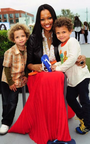 Garcelle Beauvais with her children in a floor-length pleated red skirt with a collared shirt and a black biker jacket
