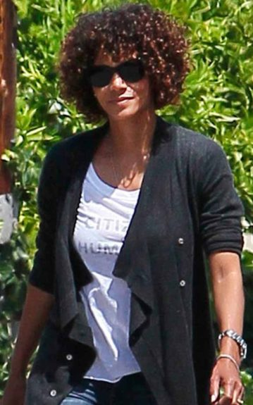 This time, Halle Berry wears her curls in a bowled bob with a bang and colored auburn strands throughout her head