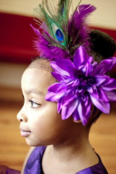 An untraditional flower girl. Her peacot fascinator accented with a touch of jewelsbrings the perfect combination of classic and chic
