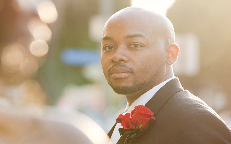 The groom Tron Miles is daper in a black tuxedo with a red rose on his lapel
