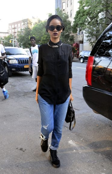 Rihanna spotted in New York City in jeans, a black blouse, pigtail buns, and a pair of Le Specs Muffin Top Sunglasses.