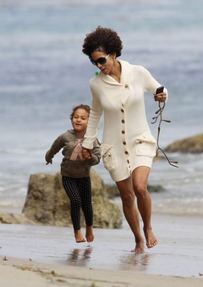 Halle Berry holds hands with her daughter Nahla while playing at a beach in Malibu, California.