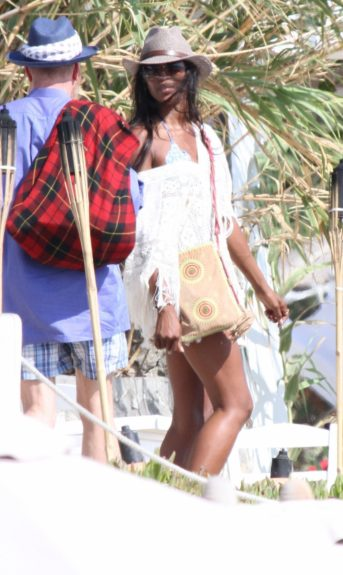 Naomi Campbell hangs out with a mystery man on the beach at Mykonos, Greece.