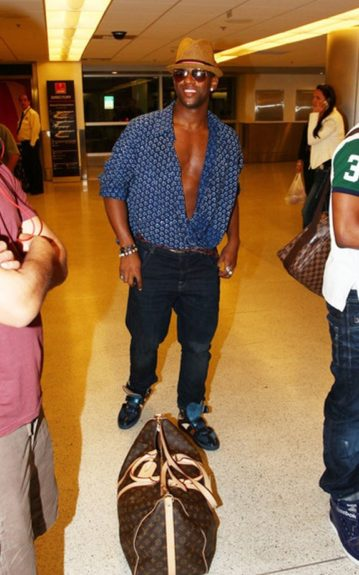 Ortise Williams of JLS posed in the airport in a button down, printed top, dark wash jeans and a pair of sneakers and accessorized with a straw fedora and aviators