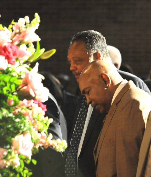 """Rev. Jesse Jackson surrounded by the pink flowers that adorned the service.  <span style=""""color: rgb(0, 0, 0); font-family: Calibri; font-size: medium;"""">Credit: John H. White</span>"""