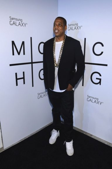 Jay-Z wore a crisp look in a white t-shirt, black blazer, dark jeans, white sneakers, and chunky gold chain. <em>photo: Getty</em>