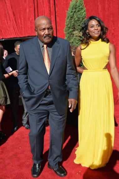 Hall of Famer Jim Brown, poses with his beautiful wife, Monique and we're loving her yellow gown