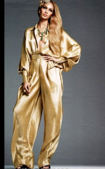 Joan Smalls looks amazing in a wide legged gold pants jumper, and gold hair accessory, and green and gold necklace.