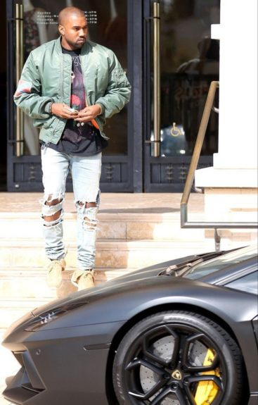 Rocking his <em>very</em> controversial clothing line from his Yeezus tour featuring the confederate flag, West does a little shopping in the Big Apple in a green bomber, Yeezus t-shirt, ripped jeans, and tan Visvim sneakers.